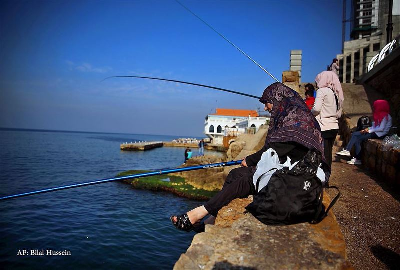 Lebanese fisherwomen sit on a breakwater along the Beirut coastline, as...