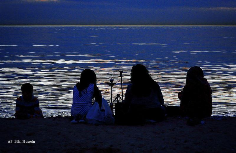A Lebanese family sits as they smoke a water pipe on the beach at the...