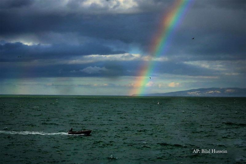 A Lebanese fisherman in his boat on the Mediterranean Sea as a rainbow...