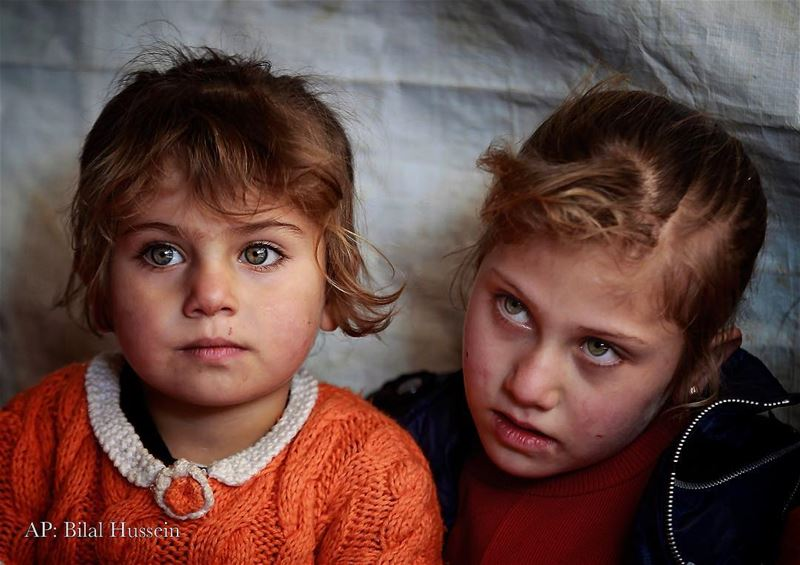 Syrian refugee Eman al-Aqraa, 8, right, and her sister Fatima, 4, listen...