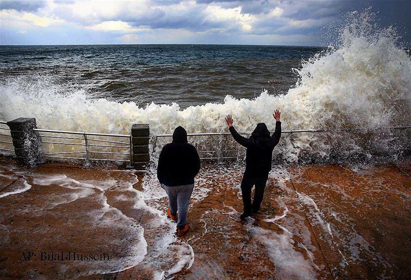Lebanese men watch waves break at the Corniche wall, in Beirut, Lebanon,...