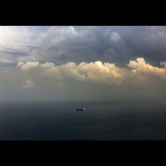 A cargo ship navigates in the Mediterranean Sea under heavy clouds along...