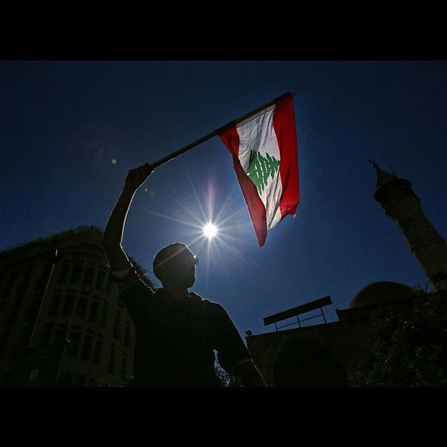 A right-wing Christian Phalange Party supporter waves a Lebanese flag...