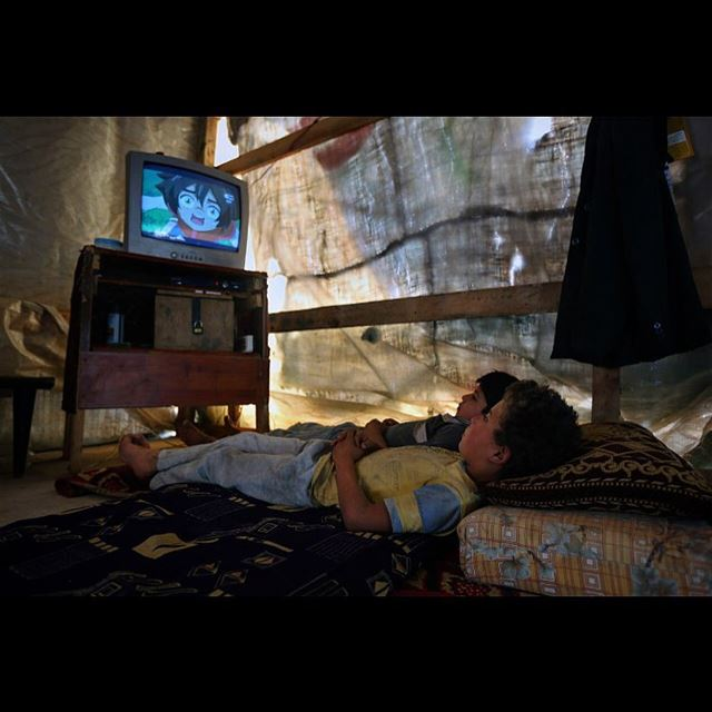 Syrian refugee boys watch television inside their family's tent at a...