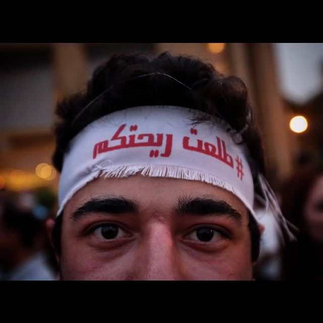 A Lebanese anti-government protester wears a headband with Arabic that...