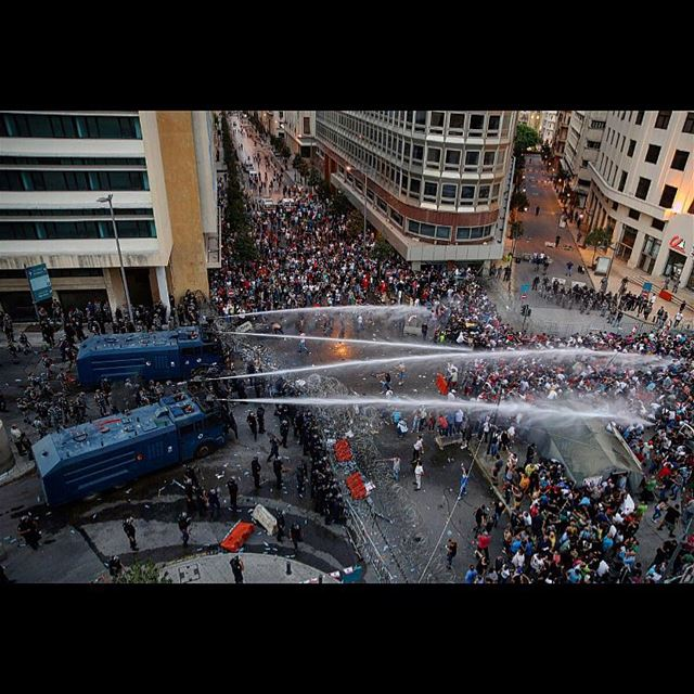 Lebanese activists shout anti-government slogans as they are sprayed by...