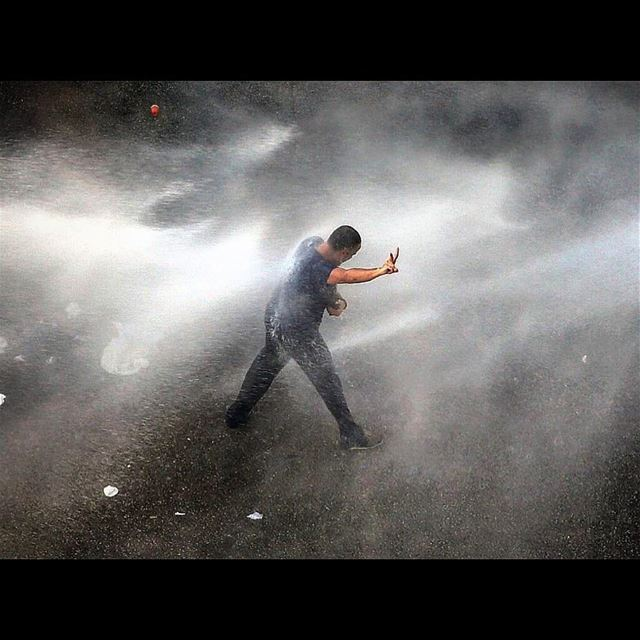 A Lebanese activist is sprayed with water, by riot police, while he tries...