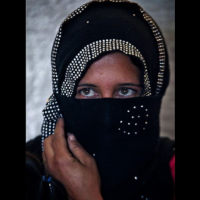 A Syrian refugee woman speaks during an interview with The Associated...