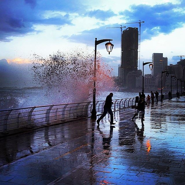 People watch high waves crashing on the seafront, at the corniche in...
