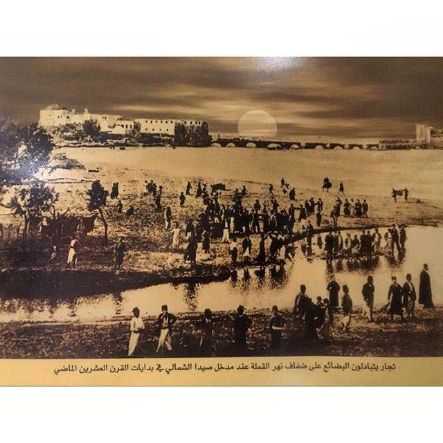 تجار يتبادلون البضائع على ضفاف نهر القملة عند مدخل صيدا الشمالي في بدايات القرن العشرين الماضي .
