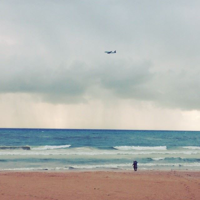 People playing on the beach and a plane passing by scene love storm ...