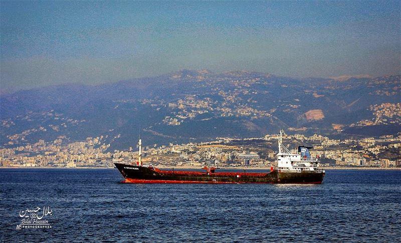 A cargo ship navigates in the Mediterranean Sea along the Beirut coastline,