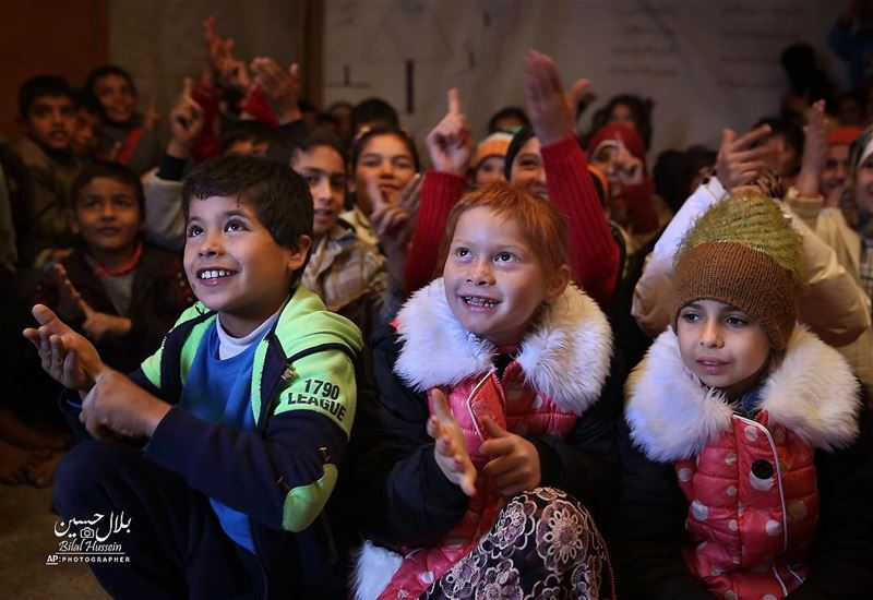Syrian refugee children respond to their teacher inside a tent that has...